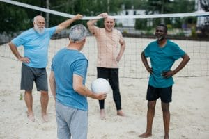 seniors playing a game of beach volleyball