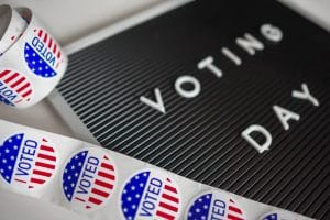 "sign saying ""voting day"" with ""I voted"" stickers"