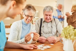 elderly couple playing a puzzle