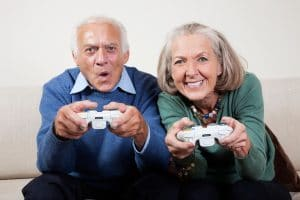 senior couple smiling excitedly while sitting down holding white video game controllers