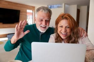 senior couple smiling and waving at laptop screen