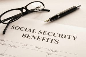 """social security benefits"" written on piece of paper with black glasses and a black pen above it"